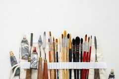 Paintbrushes, palette knifes and paint tubes in textile carry bag. A storage case filled of tools for professional artist work. Royalty Free Stock Image