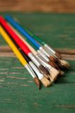 Paintbrushes placed on green worn wooden board Stock Photography