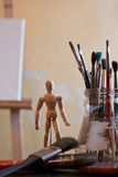 Wooden doll. Paintbrushes and small wooden doll Stock Photos
