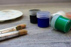 Paintbrushes, stubarwne akwareli farby i łóżko paleta na popielatym tle jako rysunkowy pojęcie Obraz Royalty Free