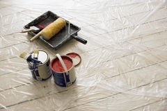 Paintbrushes, tins of paint, roller and tray on plastic sheet on wooden floor (still life) Stock Photo