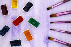 Paintbrushes and watercolor cuvettes on purple backgrounds. Stock Photo