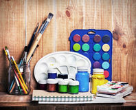 Paintbrushes, watercolor, gouache and paper are on wooden shelf Royalty Free Stock Photography