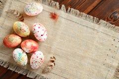 Painted покрасил пасхальные яйца на холсте на деревянной предпосылке стоковое изображение