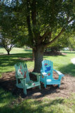 Painted Adirondack Chairs. Two beautifully painted adirondack chairs sit in the shade of a tree in Overland Park's Arboretum and Botanical Gardens Stock Photography