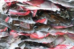Painted arrug? trozos de papel en la superficie de una pared ?spera Tonos negros rojos imagenes de archivo