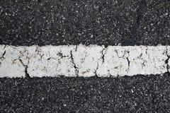 Painted Asphalt Line. White, cracked paint on old asphalt road Royalty Free Stock Images