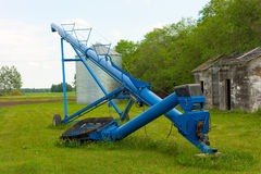 A painted auger on a farm. An agricultural tool used for transferring feed to a silo Royalty Free Stock Photo