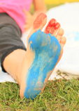 Painted bare foot of a little kid - girl. Bare foot of a little kid - girl painted on blue and red stock images