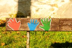 Painted bench. Colorful pictures of hands on a bench made of wood stock images