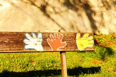 Painted bench. Colorful pictures of hands on a bench made of wood royalty free stock photos