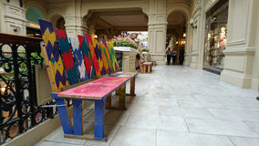 Painted bench. In different colors, handmade. GUM -Department store, Moscow, Russia stock images