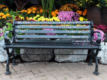 Painted Bench With Flowers In Greenhouse. Bench painted with flowers in front of a floral display in greenhouse royalty free stock photo