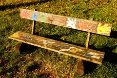 Painted bench. Wooden bench in the park, human hands painted on a wooden bench stock photos