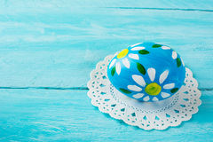 Нand-painted blue Easter egg. With floral design on a blue wood plank background. Easter background. Easter symbol. Copy space Royalty Free Stock Photo