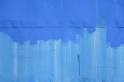 Painted blue metal with rivets. An uneven painted blue wall royalty free stock image