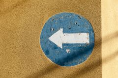 Painted blue and white one way sign on a street wall. Painted blue and white one way sign on a yellowish street wall stock photo