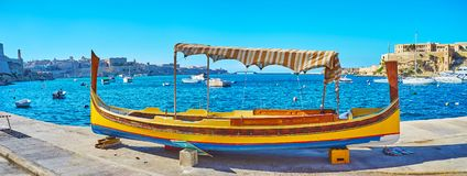 The painted boat on Birgu shore, Malta. The freshly painted and restored traditional wooden dghajsa water taxi dries ashore with a view on Kalkara marina on Royalty Free Stock Photography
