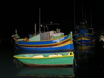 Painted boats in harbor, Marsaxlokk, Malta. Painted fishing boats in harbor of Marsaxlokk, Malta at night Stock Image
