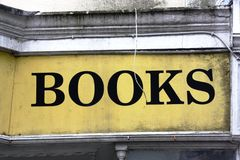 Painted books sign on wall - grunge. A yellow and black books sign on a building that is dirty and crumbling Stock Photos