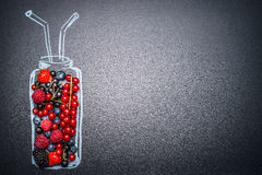 Painted bottle with fresh various berries for smoothie or juice making on dark chalkboard background Royalty Free Stock Photo