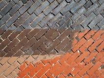 Diagonal brick wall, blue brown and orange paint stock photos