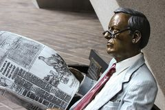 Painted bronze statue of a man reading a newspaper stock photography