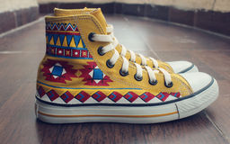 Painted Canvas Shoes. Hand Painted Aztec Canvas Shoes Royalty Free Stock Photography