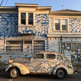 A painted car that comes with a matching home. A car with clouds painted on it is parked in front of a similarly painted house in Berkeley, California Stock Images