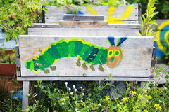 Painted caterpillar on wooden board in garden Royalty Free Stock Photo