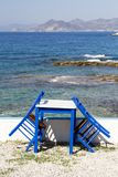 Painted chairs and table by the sea Stock Photography