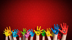 Painted children hands with smiley in front of christmas background. Painted children hands with smiley in front of a christmas background Stock Photos