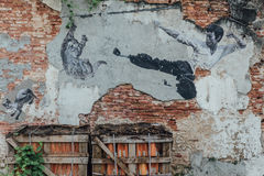 Painted Chinese Man Jumping Kick Cat in The Air on Old Red Brick Wall from The Street of George Town. Penang, Malaysia.  Royalty Free Stock Photos