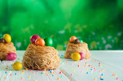 Painted chocolate eggs in sweet nests over white wooden backgrou Stock Image