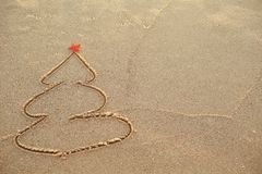 Painted Christmas tree in the sand on the beach. The concept of Christmas. Painted Christmas tree in the sand on the beach stock images