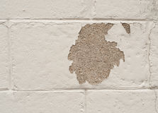 Painted cinderblock wall with missing patch. White painted cinderblock wall with a patch of missing paint Stock Photos