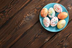 Painted colored Easter eggs on a blue plate on a wooden background stock image