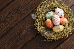Painted colored Easter eggs in a nest of hay on a wooden background royalty free stock photography