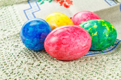 Painted colorful Easter eggs on a fabric tablecloth Stock Images