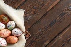 Painted coloriu ovos da páscoa na lona na caixa de madeira escura no fundo de madeira imagens de stock royalty free