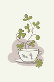 A painted cup with a stylized branch of clover and traces of bare feet of a leprechaun. Eps-8 vector graphics Royalty Free Stock Images