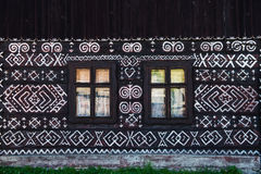Painted decorations on wall of log house in Cicmany, Slovakia. Unique decoration of log houses based on patterns used in traditional embroidery in village of Stock Photo