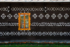 Painted decorations on wall of log house in Cicmany, Slovakia. Unique decoration of log houses based on patterns used in traditional embroidery in village of Royalty Free Stock Photography
