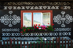 Painted decorations on wall of log house in Cicmany, Slovakia. Unique decoration of log houses based on patterns used in traditional embroidery in village of Royalty Free Stock Photos