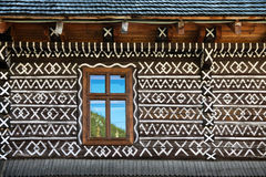 Painted decorations on wall of log house in Cicmany, Slovakia. Unique decoration of log houses based on patterns used in traditional embroidery in village of Royalty Free Stock Images
