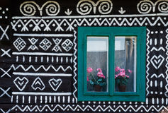 Painted decorations on wall of log house in Cicmany, Slovakia. Unique decoration of log houses based on patterns used in traditional embroidery in village of Stock Photos