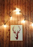 Painted deer on a wooden wall with retro garland of glowing bulbs Royalty Free Stock Image