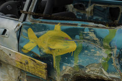 Painted Demolition Debry Car. Close up of hand-painted fish on side of beat up demolition derby car Royalty Free Stock Photo