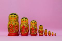 Eight matrioshka on the rose background. Painted dolls of russian tradition, from big one to small one in line royalty free stock photo