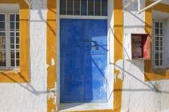 Painted door of an abandoned workshop in Pyrgos, Santorini, Greece. Stock Photos